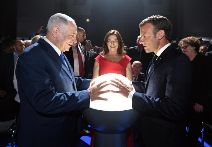 Two men face each other with their hands on a glowing orb, as a woman looks on