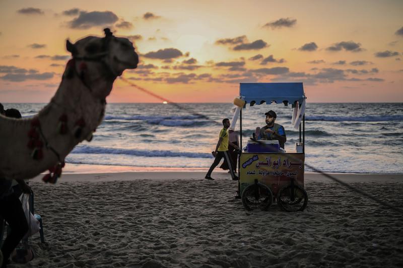 The sun sets over the sea behind a vendor on Gaza beach