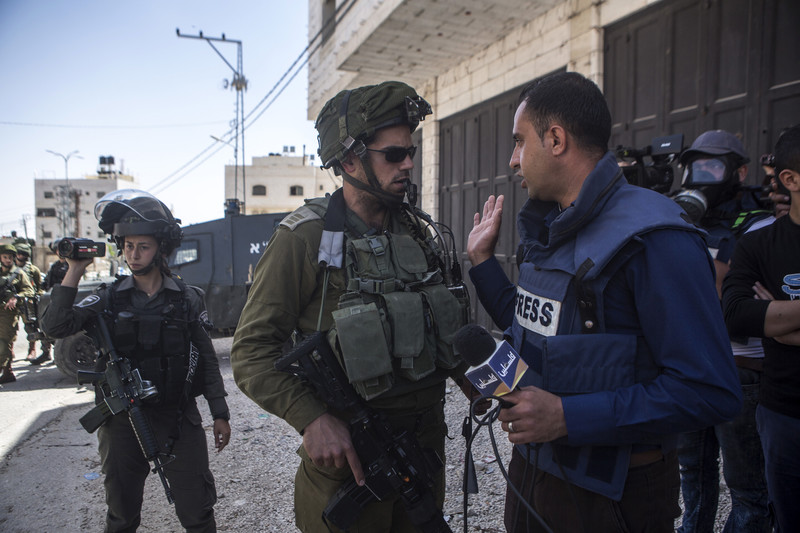 An armed Israeli soldier confronts a man wearing a press flak jacket while holding a microphone