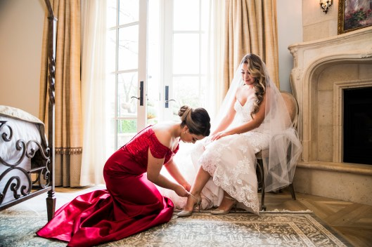 bridesmaid helping bride get ready for wedding