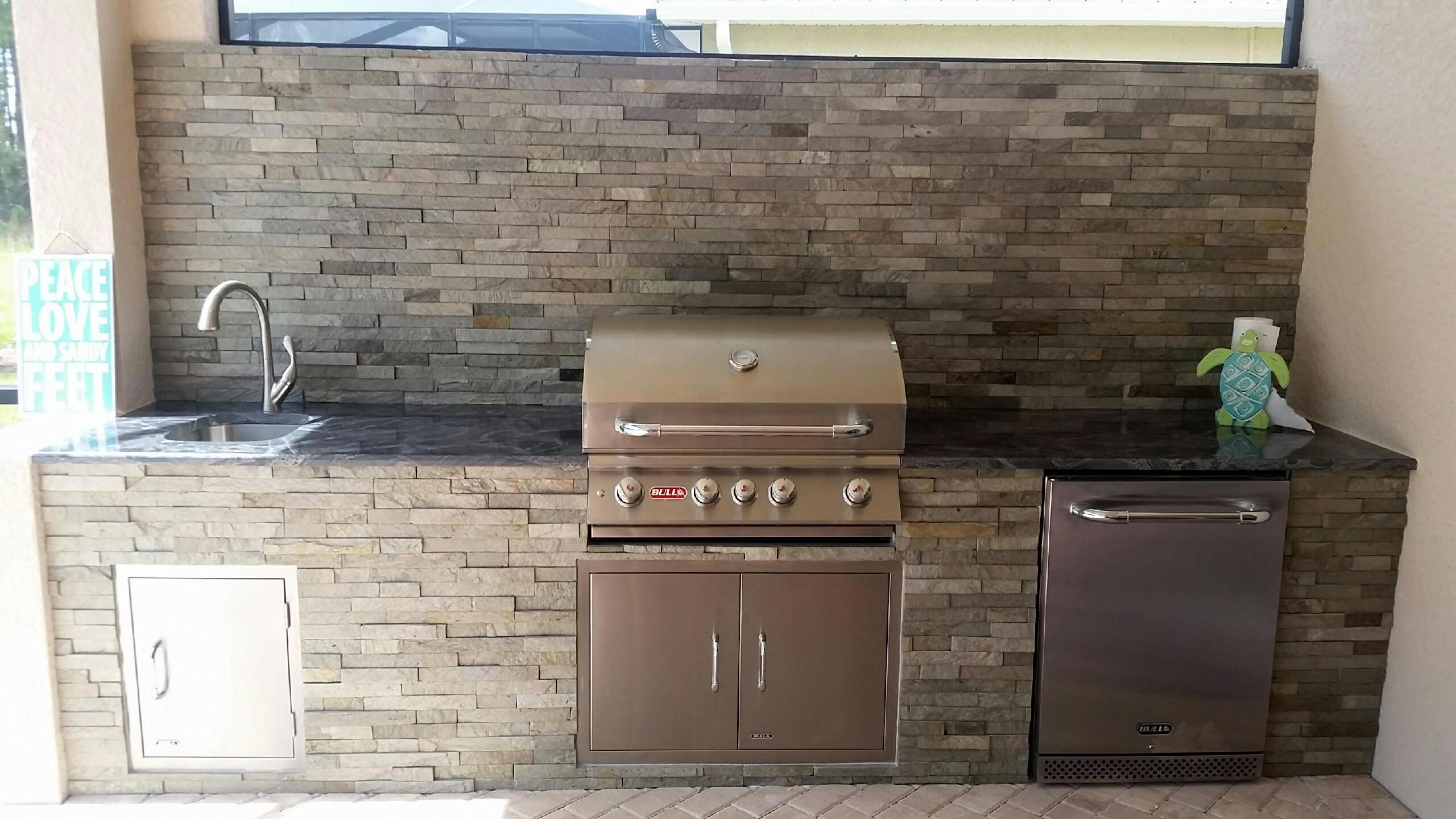 stacked stone outdoor kitchen gray chairs sophistication pelican preserve elegant