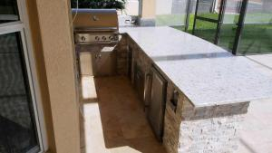 Overview of Custom L-Shaped Outdoor Kitchen by Elegant Outdoor Kitchens of SWFL