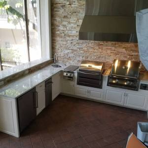 Elegant Outdoor Kitchens Custom Barbecue Island with Elegant Outdoor Kitchens Custom Barbecue Island with 2-Tier Level One Baracco White Granite Countertops, Golden White Stacked Stone, and American Outdoor Cabinets