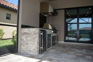 Uba Tuba Granite with Silver Travertine stacked stone Outdoor Kitchen by Elegant Outdoor Kitchens.