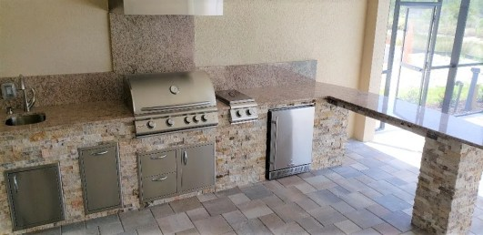 L Shape outdoor kitchen with pillar and open below bar