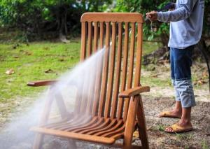 Cleaning outdoor rocking chair as part of how to refinish a wooden rocking chair