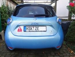 """Blauer Renault Zoe mit Aufkleber """"Emission Impossible"""", auf Magnetfolie aufgezogen. Dadurch kann der Sticker nach Lust und Laune gewechselt werden."""