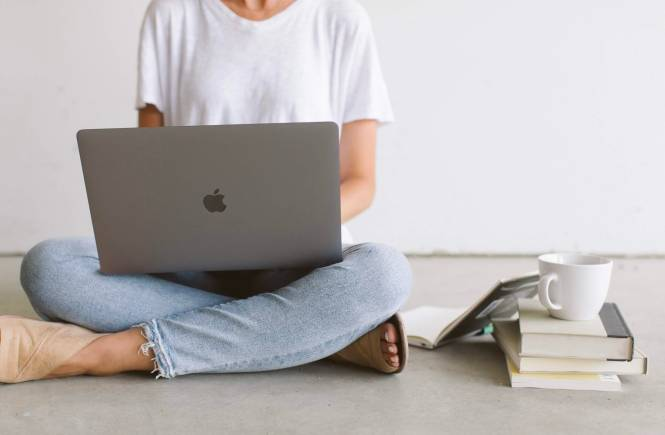 Woman working on a MacBook laptop.