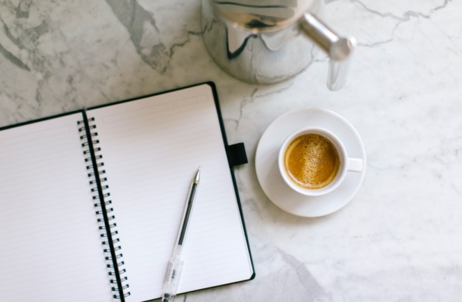 Open notebook and cup of coffee on marble tabletop. Work productively from home.