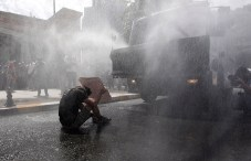 Turkish riot police use water cannon to disperse demonstrators during a protest against the destruction of trees in a park brought about by a pedestrian project, in Taksim Square in central