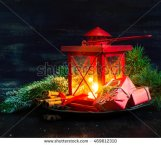 stock-photo-christmas-time-red-latern-with-candle-light-and-gifts-toned-image-469612310