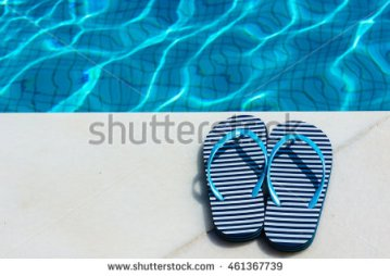 stock-photo-stripped-flip-flop-summer-shoes-on-poolside-461367739