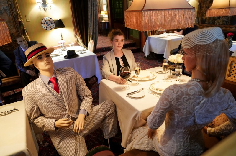 A woman sits with mannequins at a restaurant - photos of the week