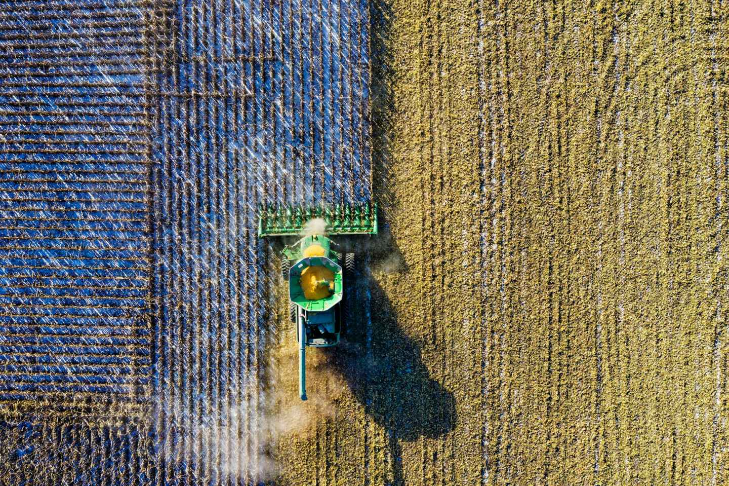 aerial shot of green milling tractor - struggling farmers
