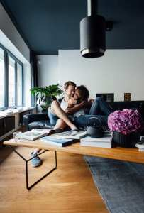 Young couple sharing an embrace on their sofa