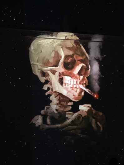 Puffs of smoke rise from a faintly glowing ember in Van Gogh's Skull of a Skeleton with Burning Cigarette.