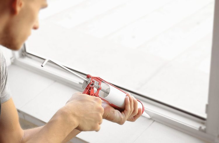 técnico reparando una ventana de aluminio con silicona