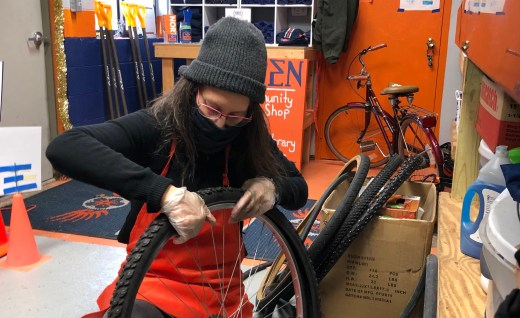 A person putting winter tires on their bike at Norte's free Community Bike Shop.