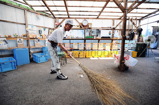 Masaru Goto, 73, sweeps up as part of his daily chores at the waste disposal site in central Kamikatsu Town in Shikoku, Japan on July 22, 2008. The town, whose residents number just over 2,000 people, has implemented a waste recycling policy that aims at eliminating waste entirely within the next 12 years and employs retired local residents to care for the waste disposal center. Photographer: Robert Gilhooly