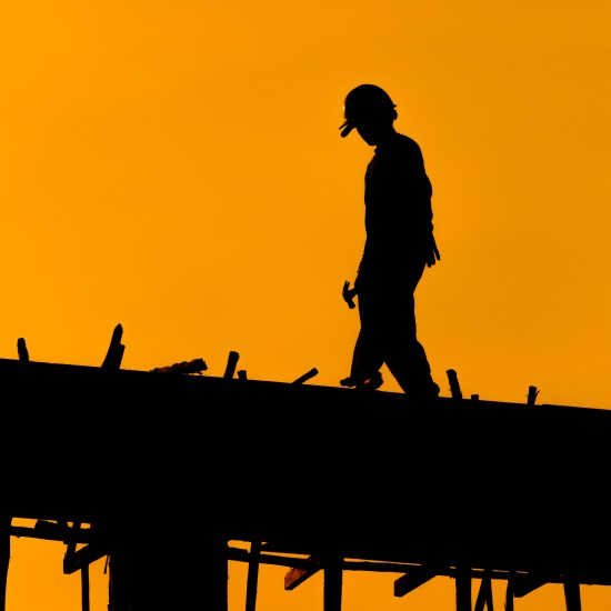 Byggnadsarbetare i solnedgång Copyright: Anan Chincho/Dreamstime.com