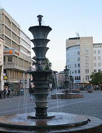Ett bråk utbryter vid fontänen på Gustav Adolfs torg och en man blir misshandlad och förd till sjukhus. Bild: sv.wikipedia.org.