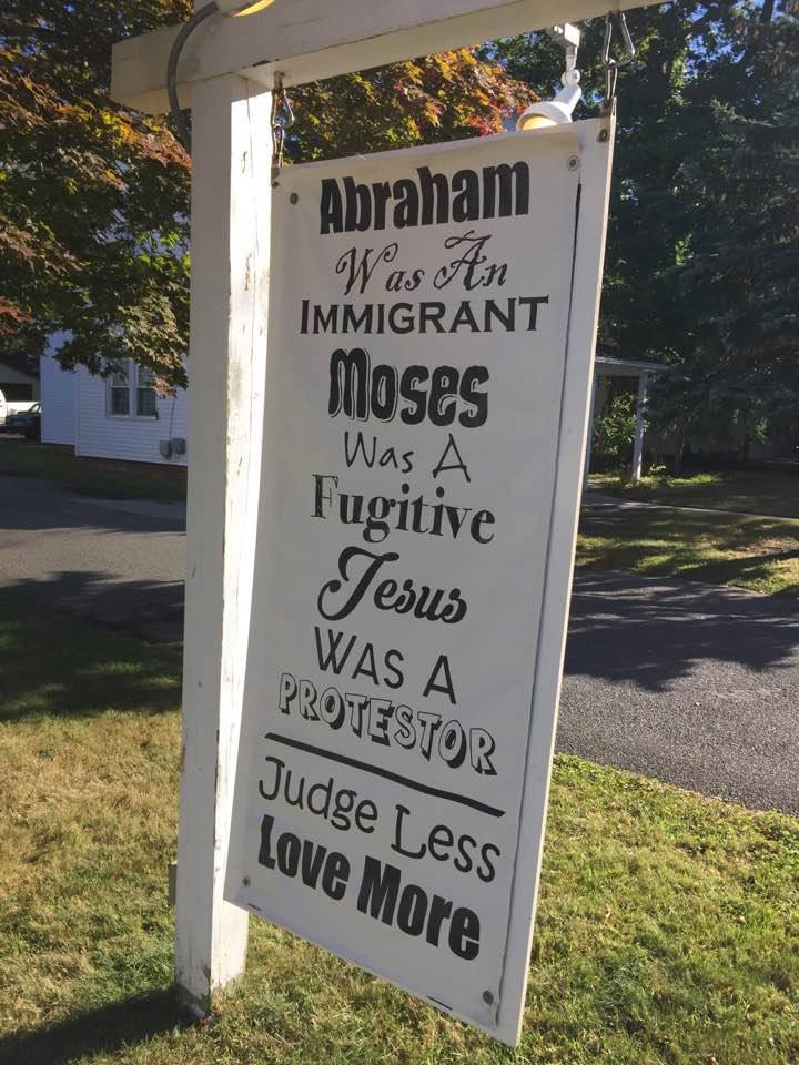Photo of hand-painted church sign: Abraham was an immigrant, Moses was a fugitive, Jesus was a protester. Judge less, love more.