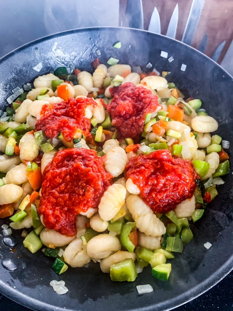 Passierte Tomaten in die Gnocchipfanne geben
