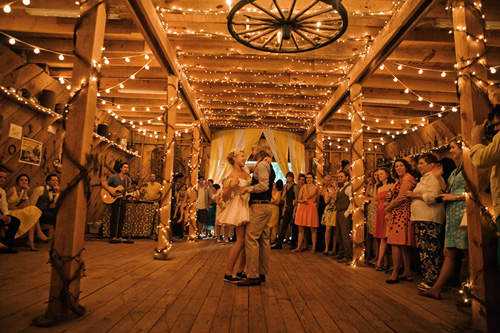 wooden wagon wheel and string lighting for a rustic barn wedding barn wedding lighting