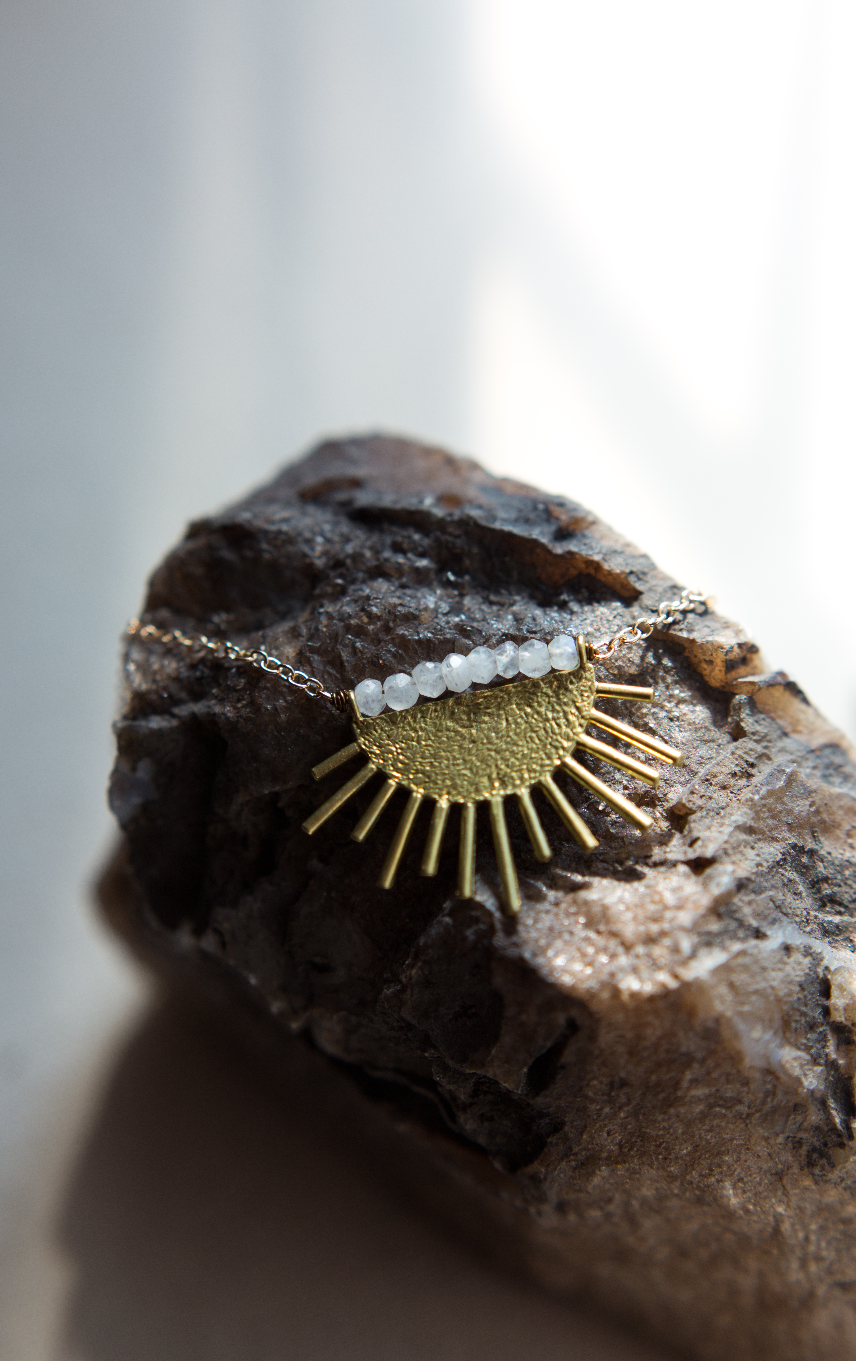 a sun pendant on a gold necklace sits on a rock. Product photography matters by Elizabeth A. Images