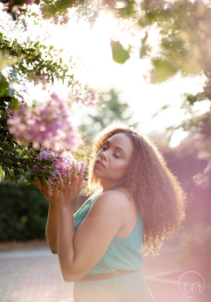 Kaela cradles a crepe myrtle blossom and closes her eyes.