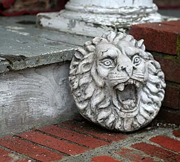 Small round stone lion face against brick steps