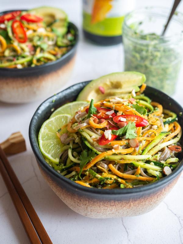 two bowls of Vietnamese pesto noodles with a jar of Vietnamese pesto and chopsticks