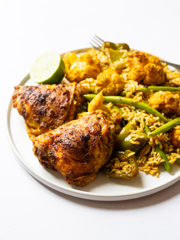 Roast Chicken Tikka Masala with vegetables and rice on a plate