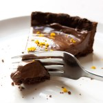 A slice of Vegan Chocolate Orange Tart being cut with a fork