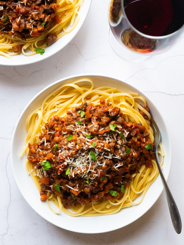 Mushroom and Lentil Spaghetti Bolognese in a white bowl with fork and a glass of red wine