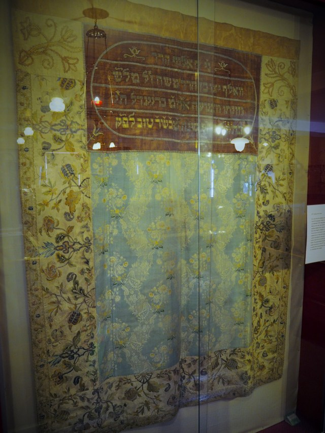 Mantel, or covering for the Torah, made from various donated clothes including a wedding dress.