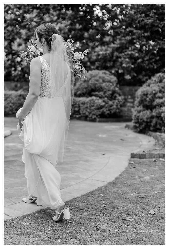 Black and White image of Bride walking down the aisle of wedding