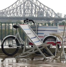 A girl can't live on chocolate alone! This bicycle cart and the deck chairs wear the livery of Chandon, an Australian sparkling wine maker. Brisbane's Story Bridge is in the background.