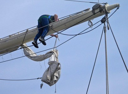 A torn sail is removed from the mast for inspection and repair.
