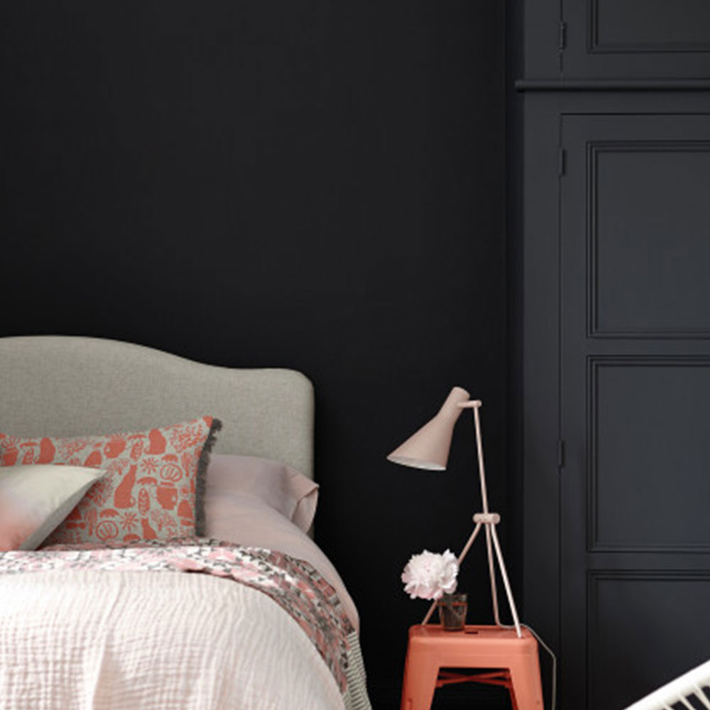 A bedside table with black wallpaper