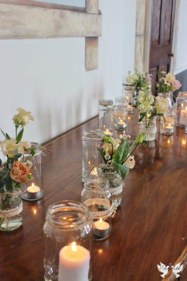 Jam jar flowers and tealights- Elizabeth Weddings