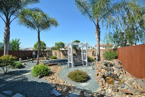 Drought friendly yard with waterfall, spa and covered patio