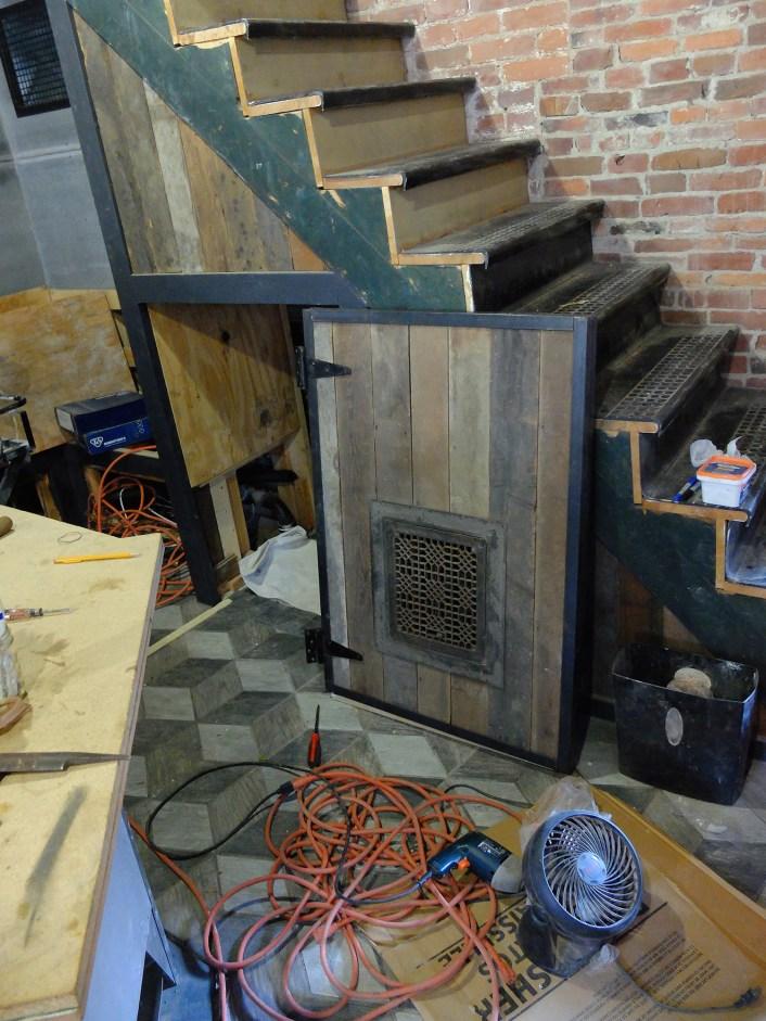 Ta da! Door trimmed with angle iron, inset floor register as a vent, old barn door hinges.