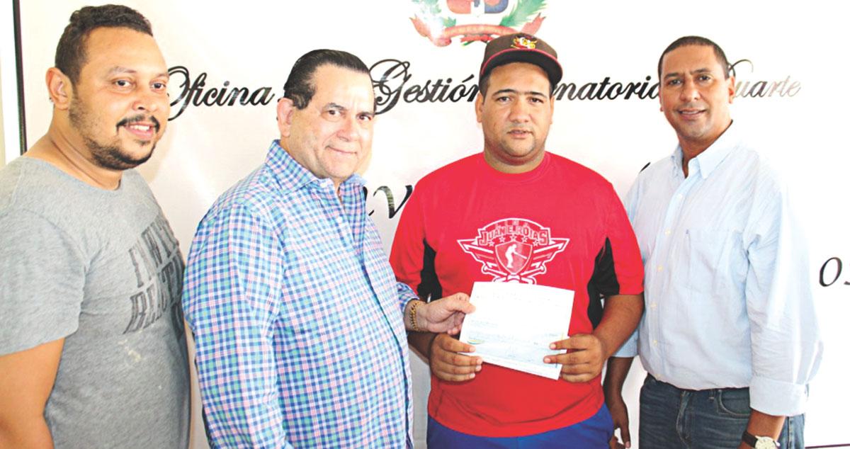 El senador Amílcar Romero entrega un aporte a Jonathan Suárez, Héctor Castillo y Juan Eligio Rojas para el equipo de las Arroceras de San Francisco en el tercer torneo nacional de béisbol femenino.
