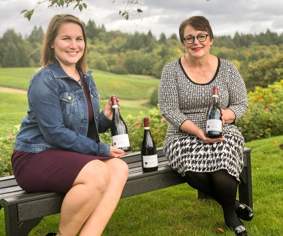 Lila and Charlotte sitting together on a bench outside with bottles of wine