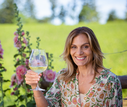 Ellie with a glass of white wine in the garden with vineyards in the background