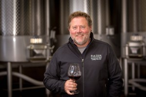 color image of winemaker Adam Campbell smiles while holding a glass of pinot noir in front of steel tanks