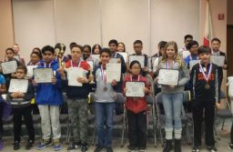 Spelling bee participants proudly showing off their certificates and medals.