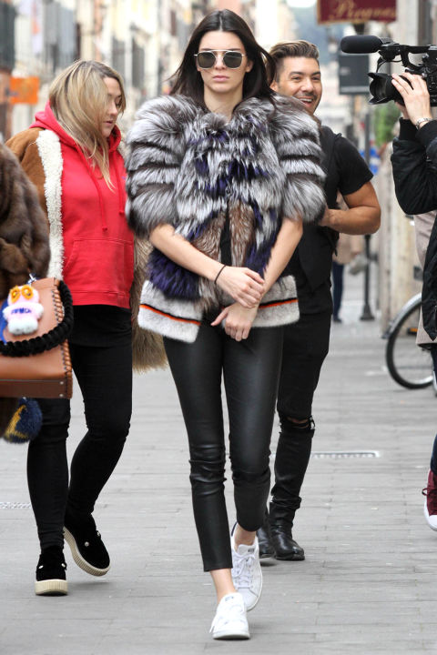 Out in Rome wearing a multi-colored fur jacket, leather leggings, and sneakers.