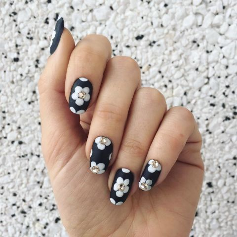 For a textured floral nail, this design mixes matte polish, regular polish and embellishments. Start with a matte base. Let dry, then paint flower petals in a glossy hue. Finish the nail with crystal accents glued to the center of each flower.  Design by @jessicawashick